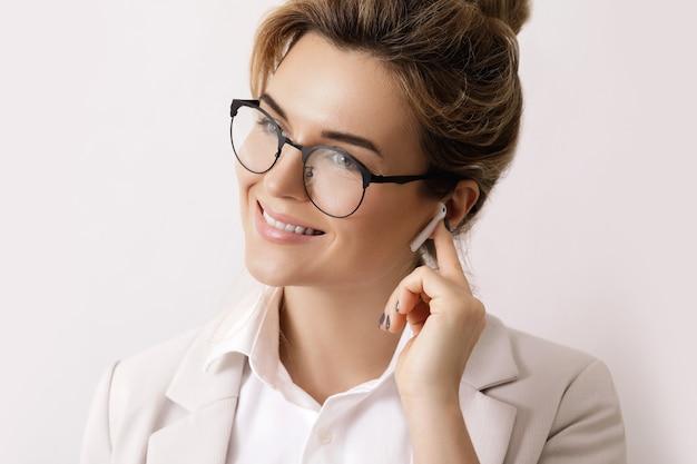 Mulher de negócios feliz com fones de ouvido sem fio nas orelhas