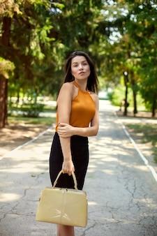 Mulher de negócios feliz com saco na mão no parque ao ar livre.
