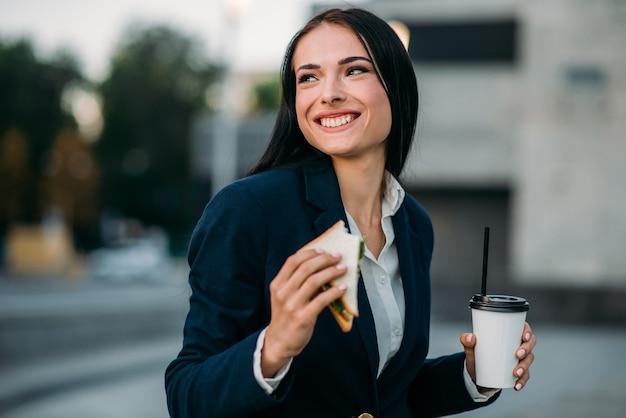 Mulher de negócios feliz com sanduíche e café nas mãos, almoço ao ar livre. edifício moderno, centro financeiro, paisagem urbana. mulher de negócios de terno no local de trabalho