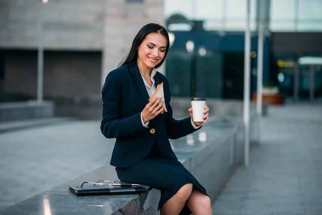 Mulher de negócios feliz com sanduíche e café