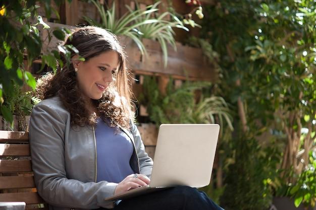 Mulher de negócios feliz com seu laptop no banco na rua