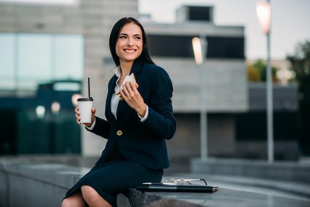 Mulher de negócios feliz de fato almoçar ao ar livre. edifício moderno, centro financeiro, paisagem urbana. mulher de negócios de terno no local de trabalho