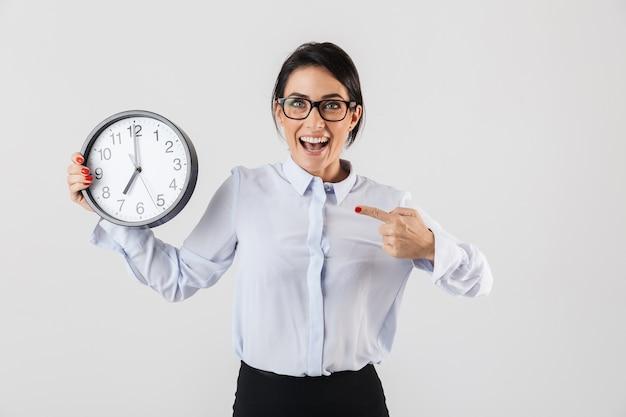Mulher de negócios feliz e animada elegantemente vestida de pé isolada na parede branca, mostrando o despertador