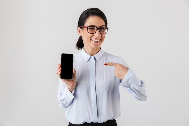 Mulher de negócios feliz e animada elegantemente vestida de pé, isolada sobre uma parede branca, apontando para um celular em branco