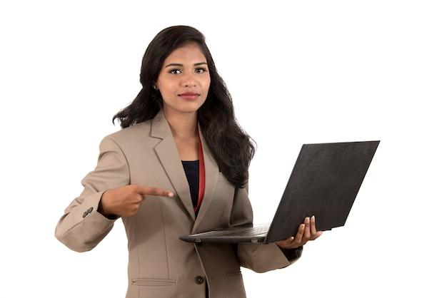 Mulher de negócios feliz e animada segurando laptop e apontando para ele, isolado em um fundo branco