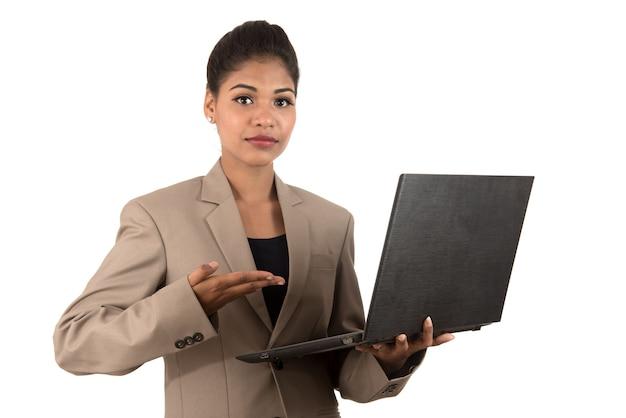 Mulher de negócios feliz e animada segurando laptop e apontando para ele isolado