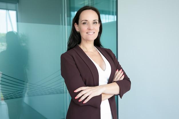 Mulher de negócios feliz e bem-sucedida de cabelos negros, vestindo terno formal, de pé com os braços cruzados e sorrindo