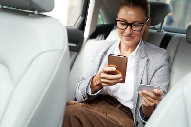 Mulher de negócios feliz e bem-sucedida usando óculos, usando seu smartphone e cartão de crédito para comprar