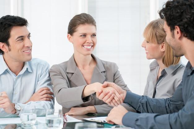 Mulher de negócios feliz e sorridente apertando as mãos após uma reunião de negócios