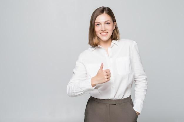 Mulher de negócios feliz e sorridente com gesto de polegar para cima, isolado na parede branca