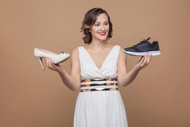 Mulher de negócios feliz em um vestido branco e segurando o tênis e o salto e sorrindo para o tênis esportivo. escolhendo sapatos confortáveis. foto de estúdio, interna, isolada em fundo marrom claro