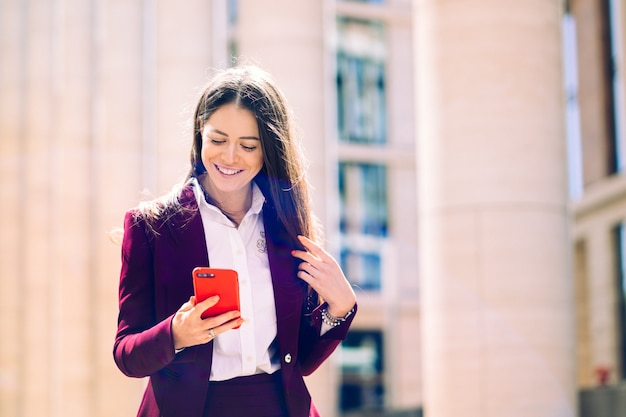 Mulher de negócios feliz lendo boas notícias em seu smartphone amplo sorriso. executivo trabalhando com um telefone móvel na rua com edifícios de escritórios em segundo plano