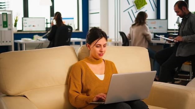 Mulher de negócios feliz lendo boas notícias no laptop sorrindo, sentada no sofá no movimentado escritório da empresa, enquanto uma equipe diversificada analisa dados estatísticos. equipe multiétnica falando sobre projeto.