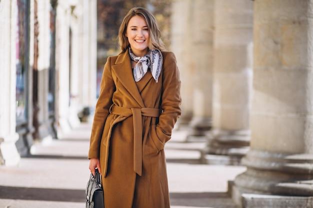 Mulher de negócios feliz no casaco na rua