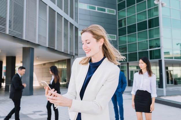 Mulher de negócios feliz olhando para o telefone inteligente