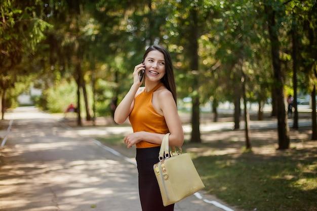 Mulher de negócios feliz ri, falando ao telefone vai no parque com um saco e olha para trás
