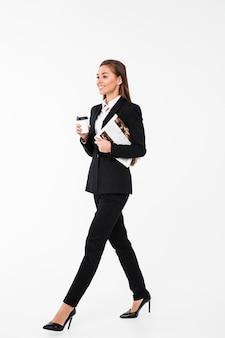 Mulher de negócios feliz segurando jornal bebendo café.