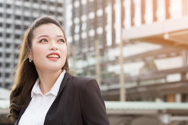 Mulher de negócios feliz sorrindo em algo imaginário