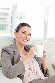 Mulher de negócios feliz tomando uma xícara de café
