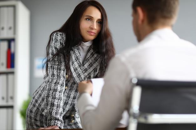 Mulher de negócios fica encostado na mesa homem da frente