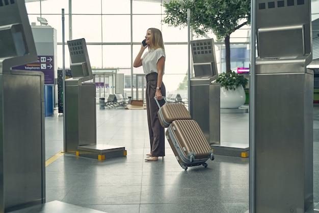 Mulher de negócios fofa expressando positividade ao falar por telefone no aeroporto, verificando o horário de partida