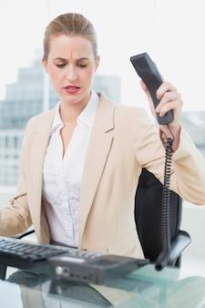Mulher de negócios furiosa bonita pendurada no telefone