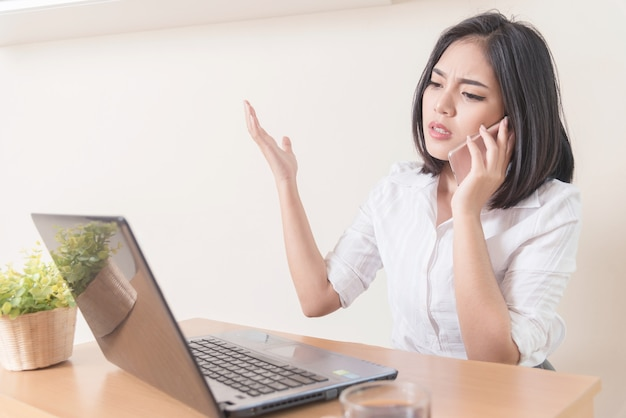 Mulher de negócios furioso vestindo terno trabalhando on-line usando um telefone inteligente em uma mesa no escritório