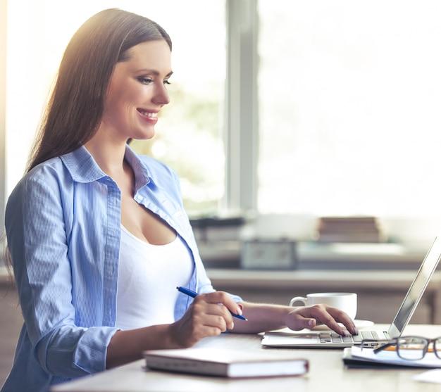 Mulher de negócios grávida bonita está usando um laptop.
