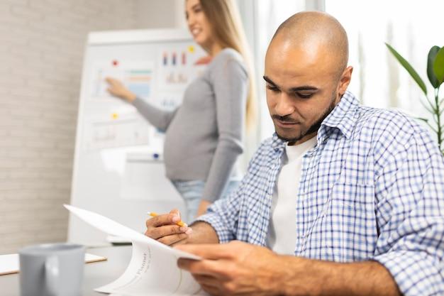 Mulher de negócios grávida fazendo uma apresentação no escritório enquanto um colega de trabalho faz anotações