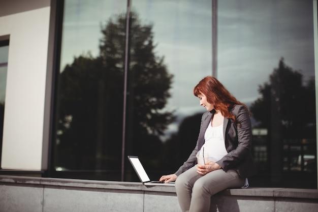 Mulher de negócios grávida usando laptop