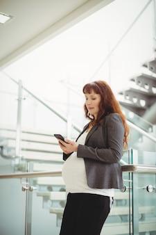 Mulher de negócios grávida usando telefone celular perto da escada