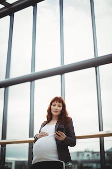 Mulher de negócios grávida usando telefone celular perto do corredor