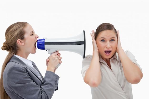 Mulher de negócios gritando com seu colega de trabalho através de um megafone