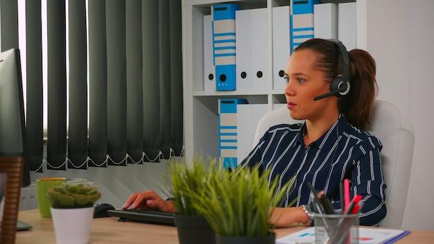 Mulher de negócios hispânica com fone de ouvido trabalhando no escritório de negócios moderno, fazendo teleappointment usando tecnologia moderna. freelancer discutindo com o cliente no prédio da empresa financeira