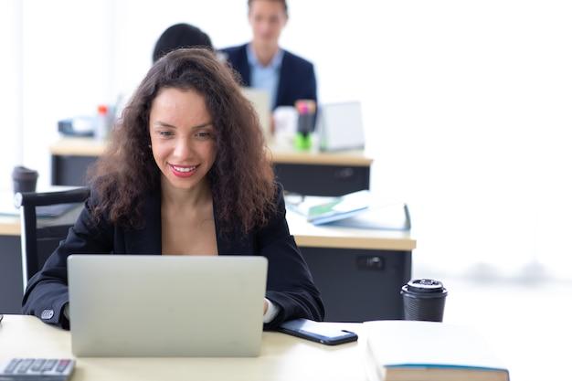 Mulher de negócios hispânica ocupada trabalhando em um laptop no escritório