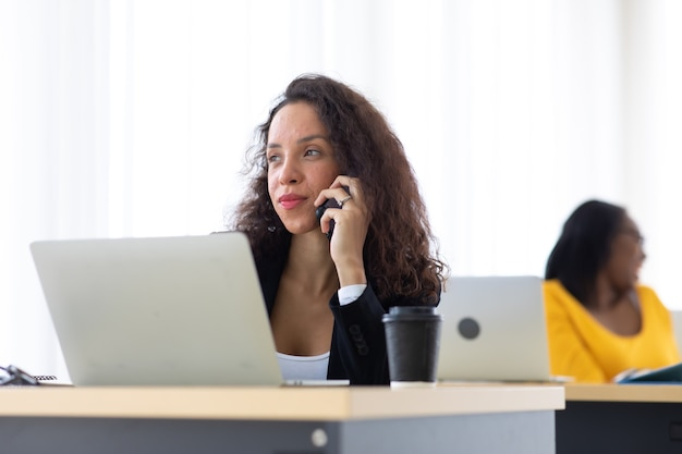 Mulher de negócios hispânicos falando no telefone móvel ocupado trabalhando computador portátil no escritório. beber café