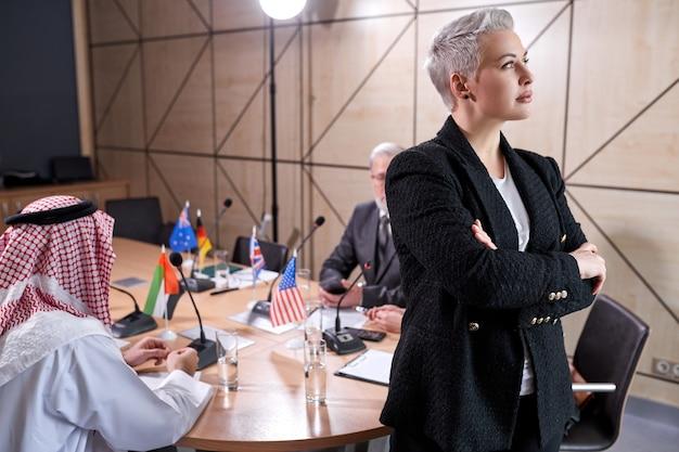 Mulher de negócios idosa com cabelo curto elegante com roupa formal, posando na sala de reuniões durante uma reunião com um grupo internacional de políticos sentados na mesa ao fundo, ela está olhando para o lado. retrato