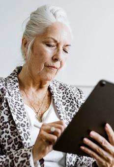 Mulher de negócios idosa tomando nota com caneta em um rablet digital