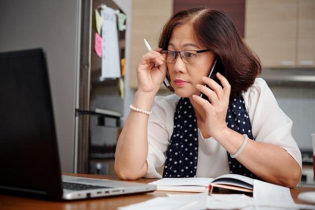 Mulher de negócios idosa trabalhando em casa, ela está usando óculos ao ler o artigo na tela do laptop e falar ao telefone