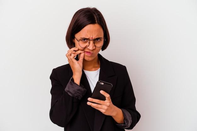 Mulher de negócios indiana jovem segurando um telefone isolado mulher de negócios indiana jovem segurando um telefone isolado com os dedos nos lábios, mantendo um segredo.