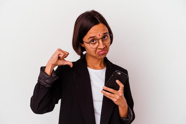 Mulher de negócios indiana jovem segurando um telefone isolado sente-se orgulhosa e autoconfiante, exemplo a seguir.