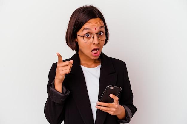 Mulher de negócios indiana jovem segurando um telefone isolado, tendo uma ideia, o conceito de inspiração.