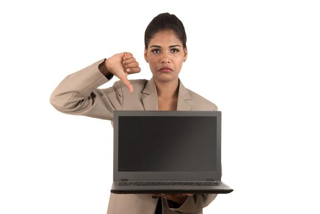 Mulher de negócios infeliz segurando laptop e mostrando os polegares para baixo isolados