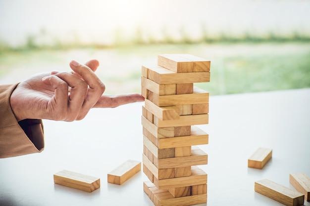 Mulher de negócios inteligente jovem jogando o jogo de madeira, mãos, colocando o bloco de madeira
