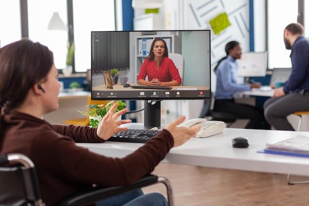 Mulher de negócios inválida e inválida, com deficiência, falando sobre relatório de venda em videoconferência, trabalhando horas extras no escritório de start-up