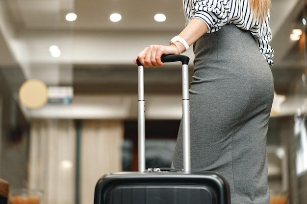 Mulher de negócios irreconhecível com uma mala de viagem perto da foto