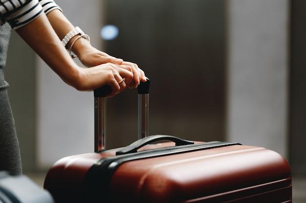 Mulher de negócios irreconhecível em pé com a mala de viagem perto