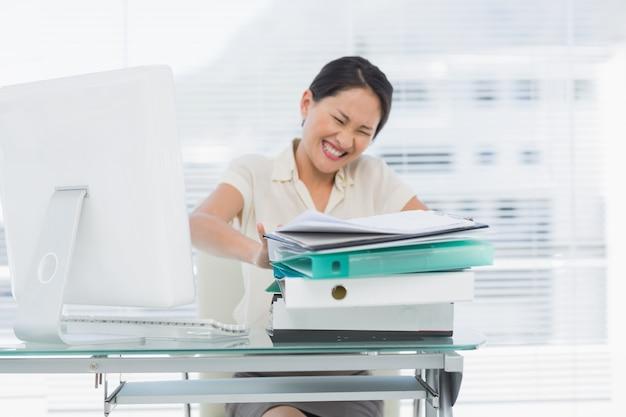 Mulher de negócios irritada com pilha de pastas na mesa