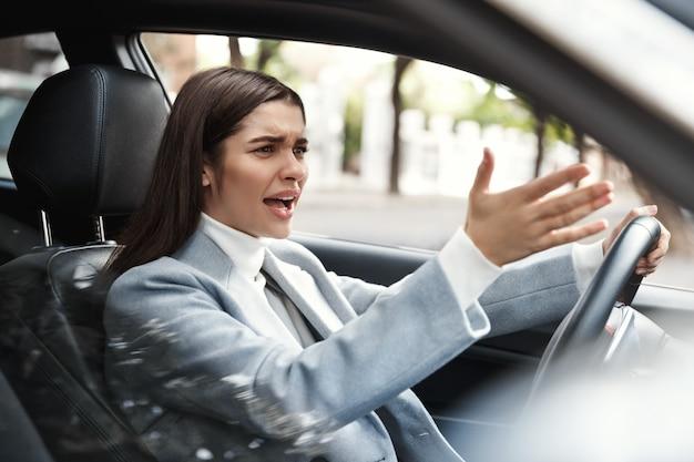 Mulher de negócios irritada preso no trânsito em seu trajeto.