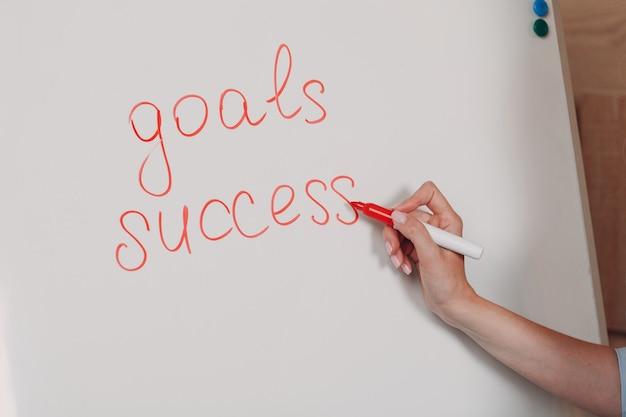 Mulher de negócios jovem adulto treinador no escritório com mão fechada com marcador no quadro branco